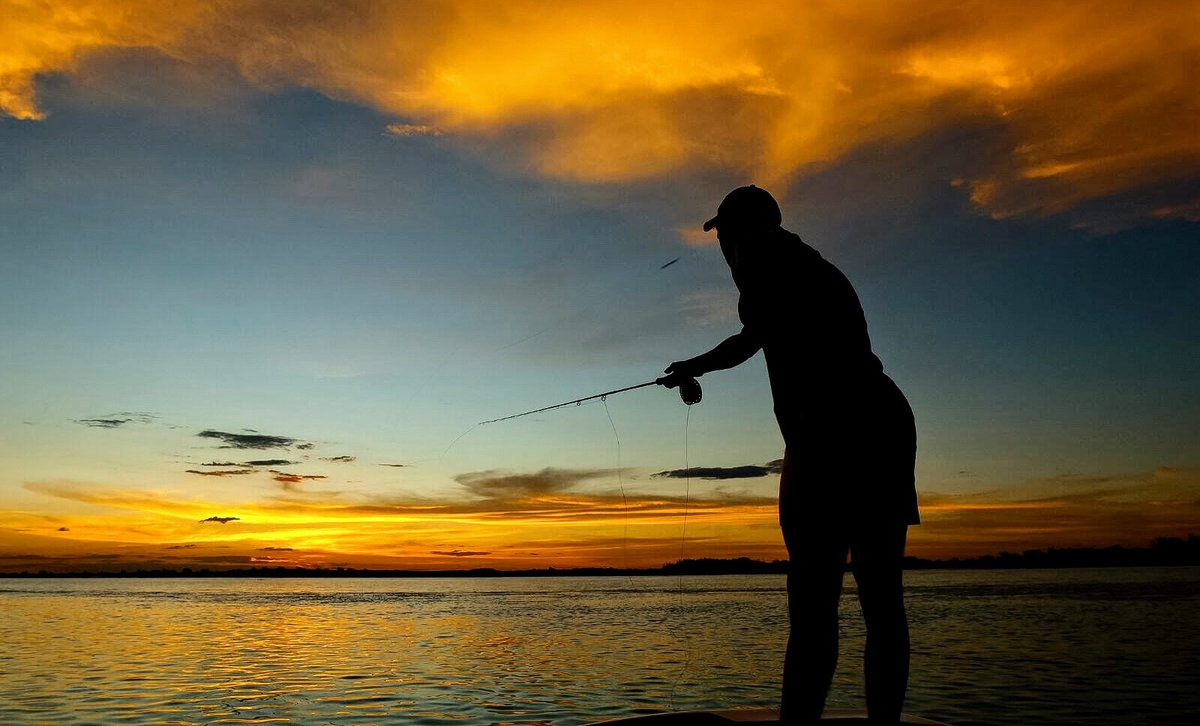 Fisherman casting out at sunset in Barotse floodplains, western Zambia