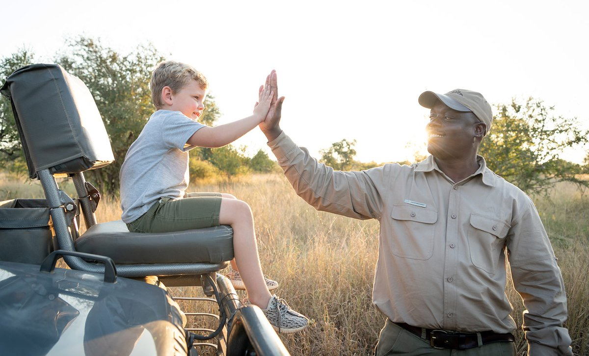 Boy on game drive vehicle with guide