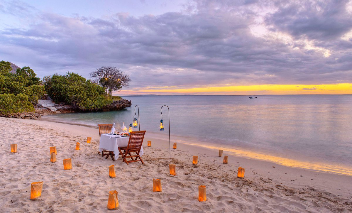 Private dining setup for two on beach at Azura Quilalea, Mozambique