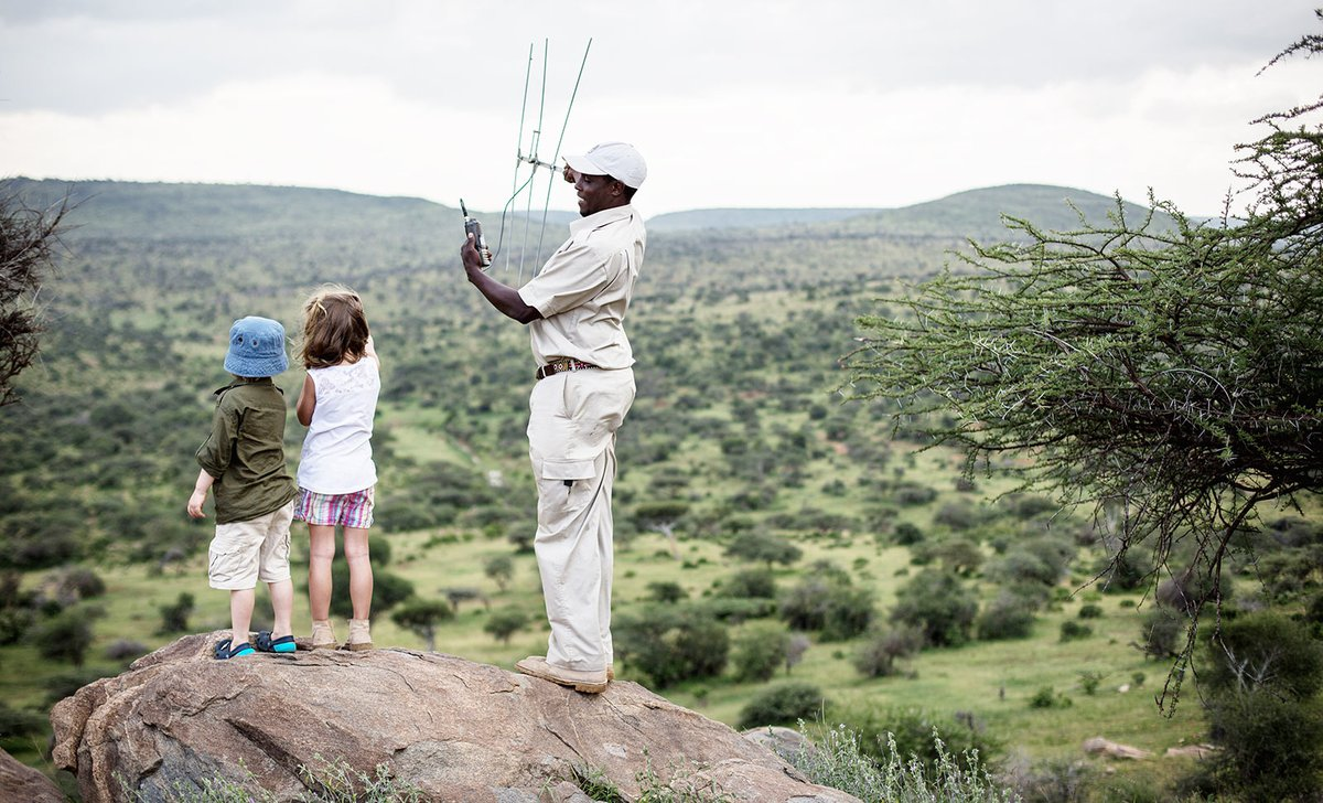 Children learning to track wildlife using radios with guide