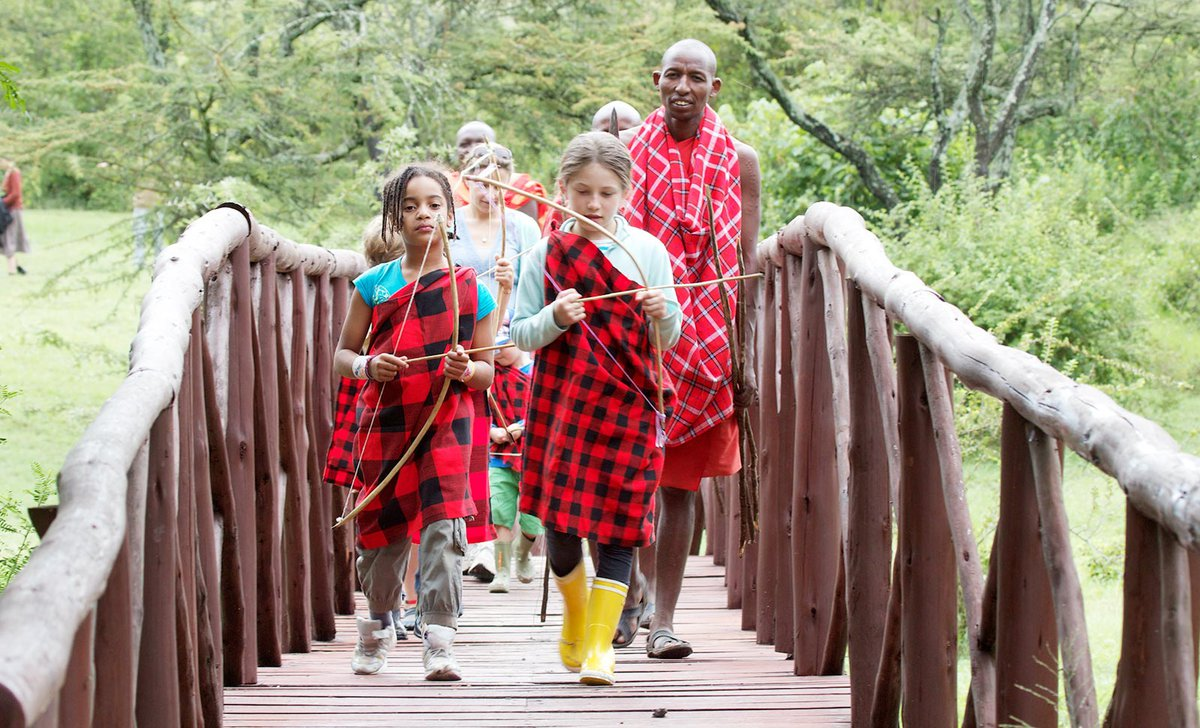 Children crossing bridge with Maasai warrior