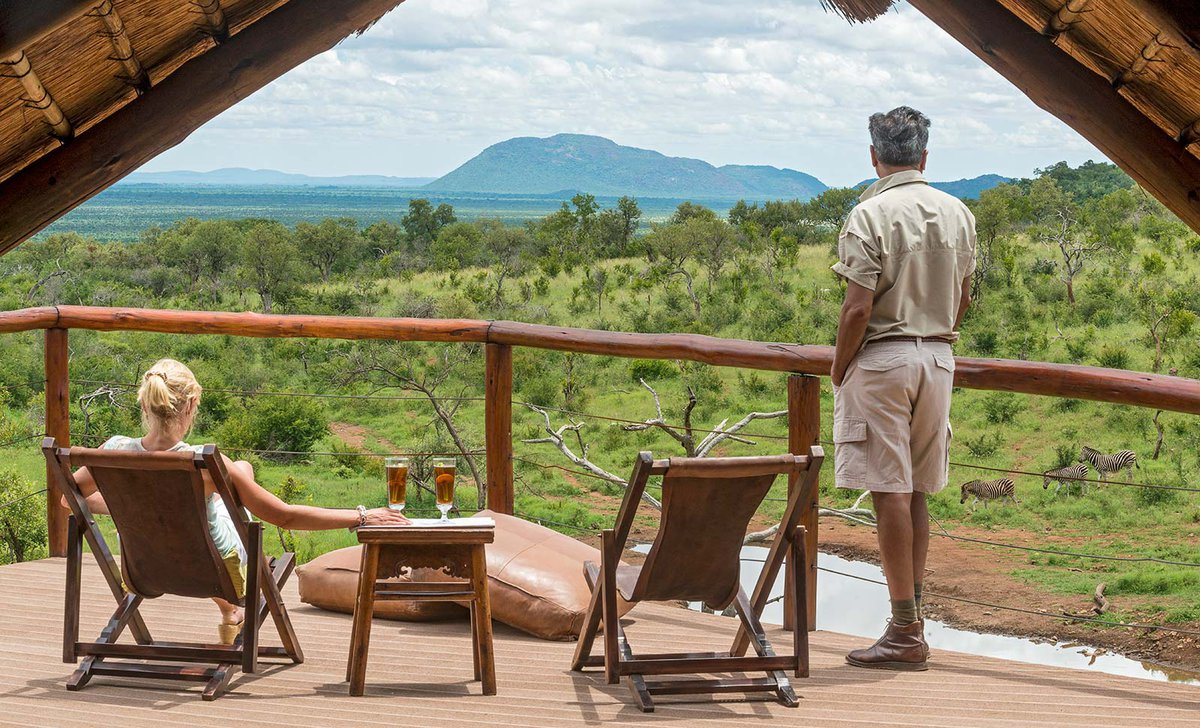 Guests watching zebras at waterhole from raised deck