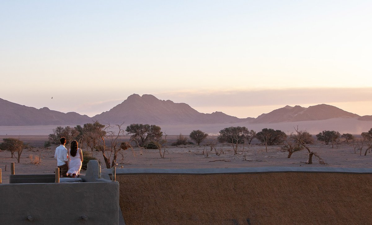 Couple looking out at Sossusvlei landscape on terrace at Little Kulala Lodge
