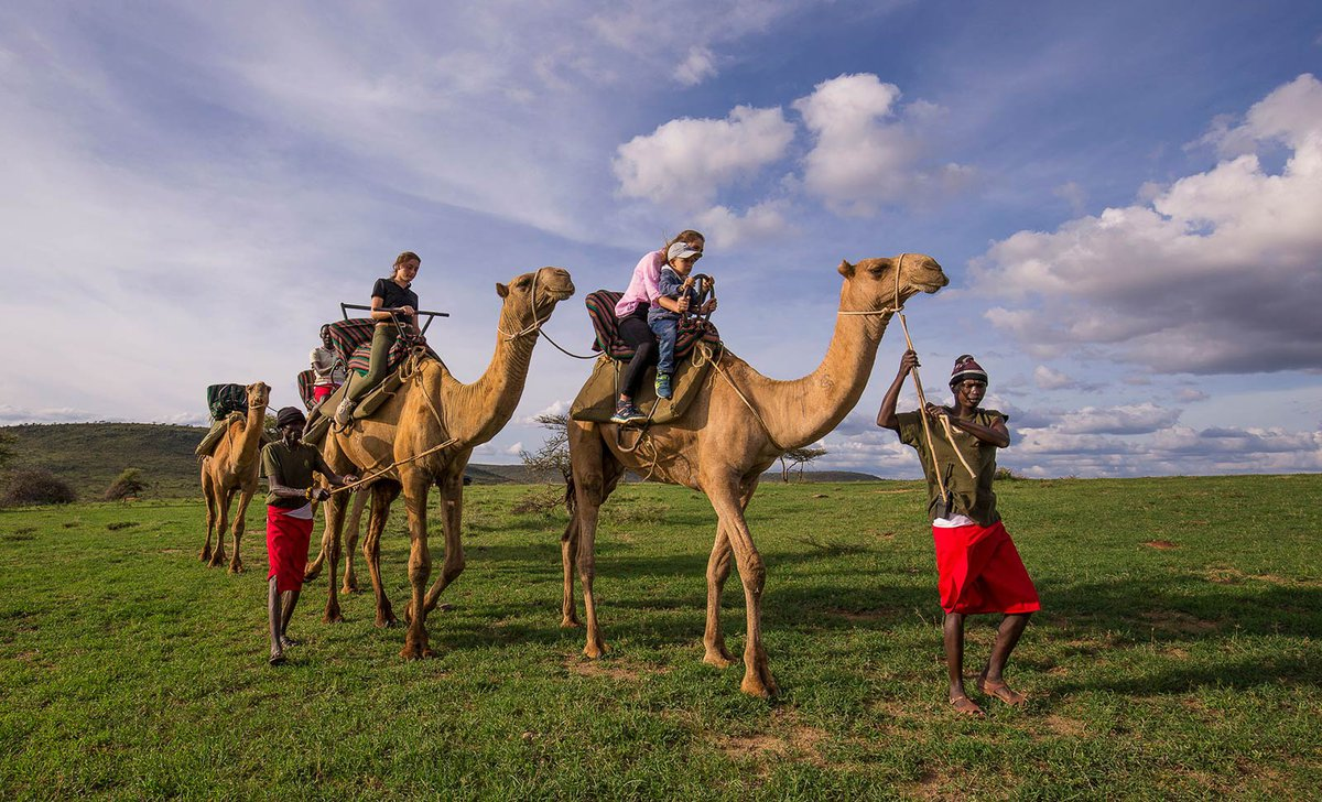 children riding camels guided by Maasai tribal members