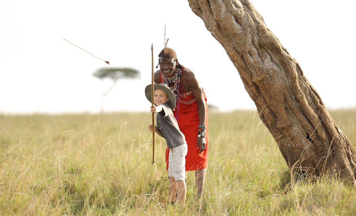 Boy shooting bow and arrow with Maasai