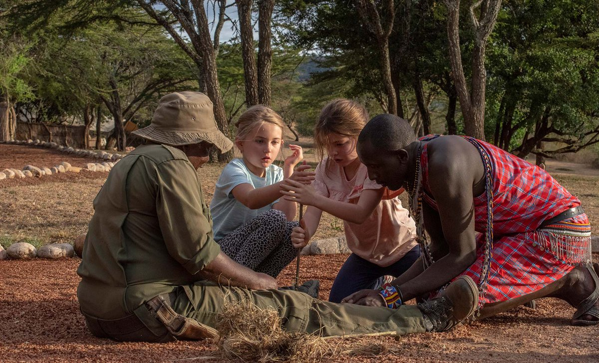 Girls learning to build fire on safari