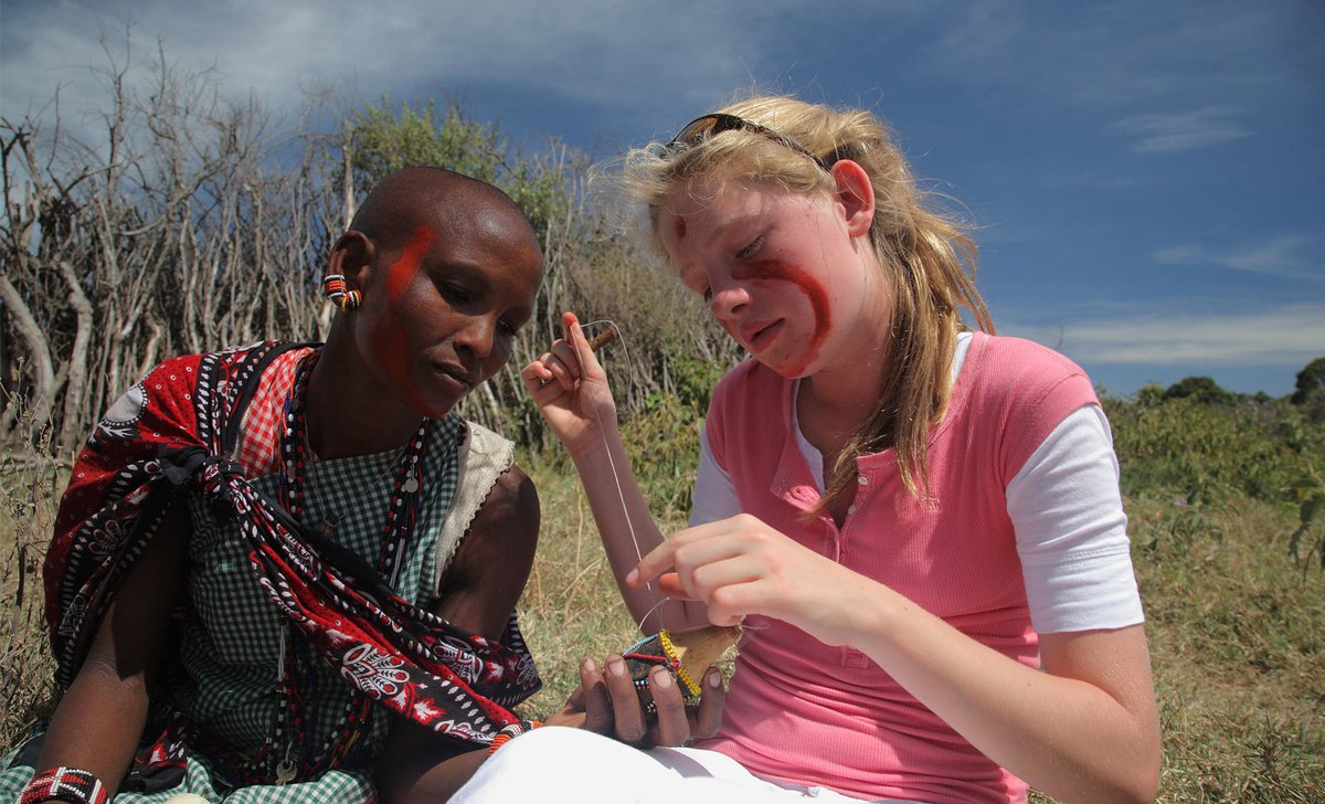 Girl learning bush craft skills on safari with Samburu warrior