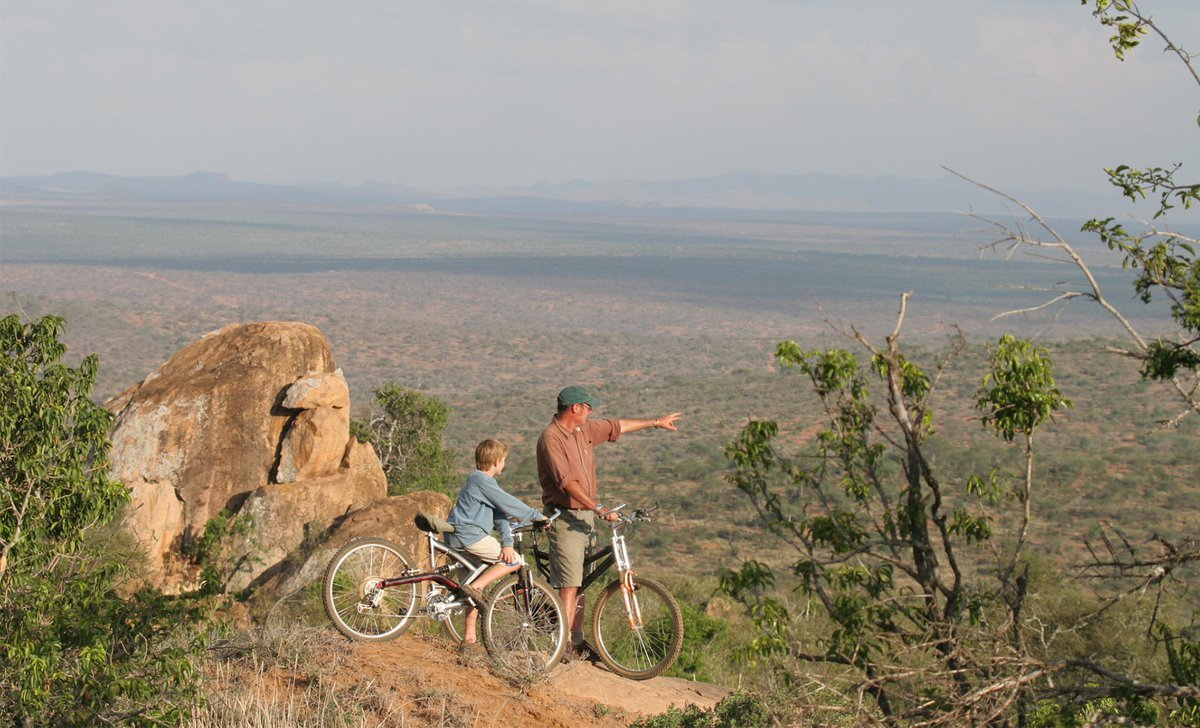 Boy and father on cycling safari in Laikipia County Kenya