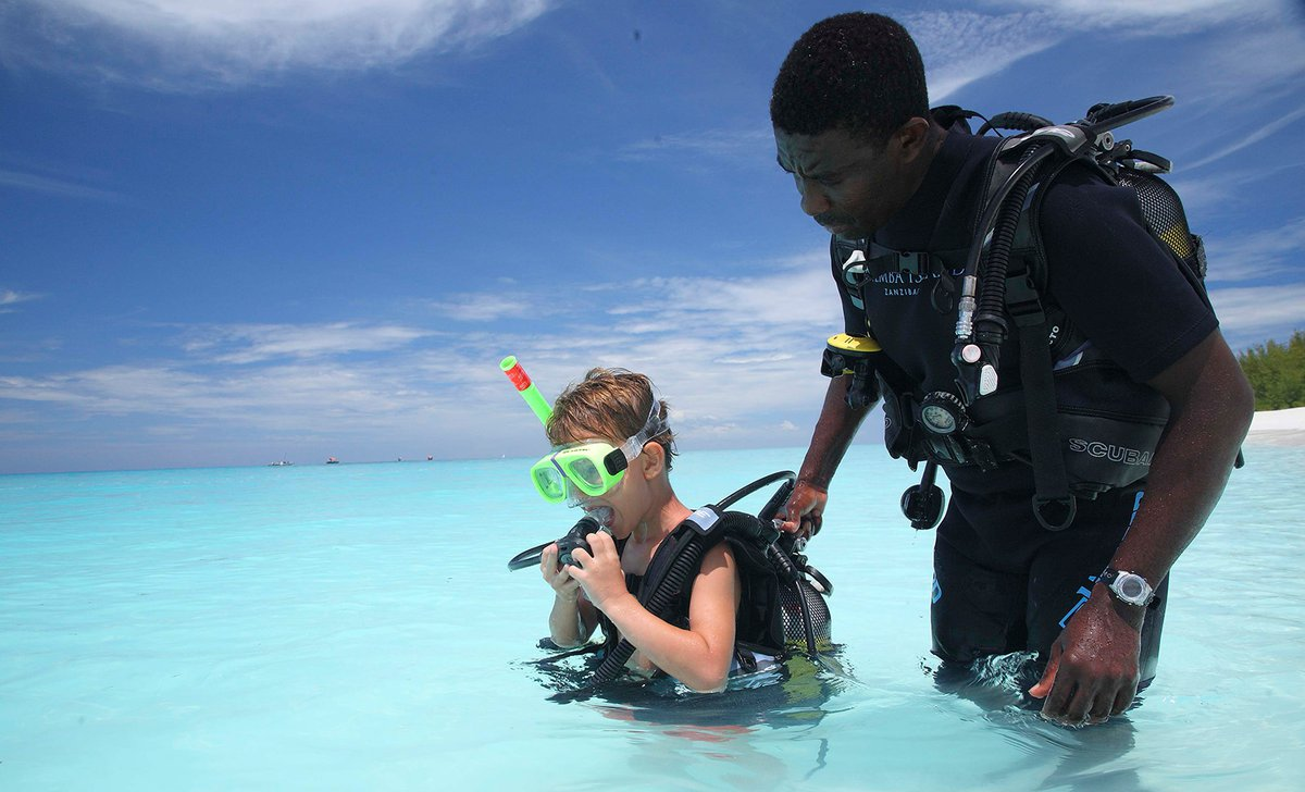 Boy learning to scuba dive with guide on Mnemba Island Zanzibar