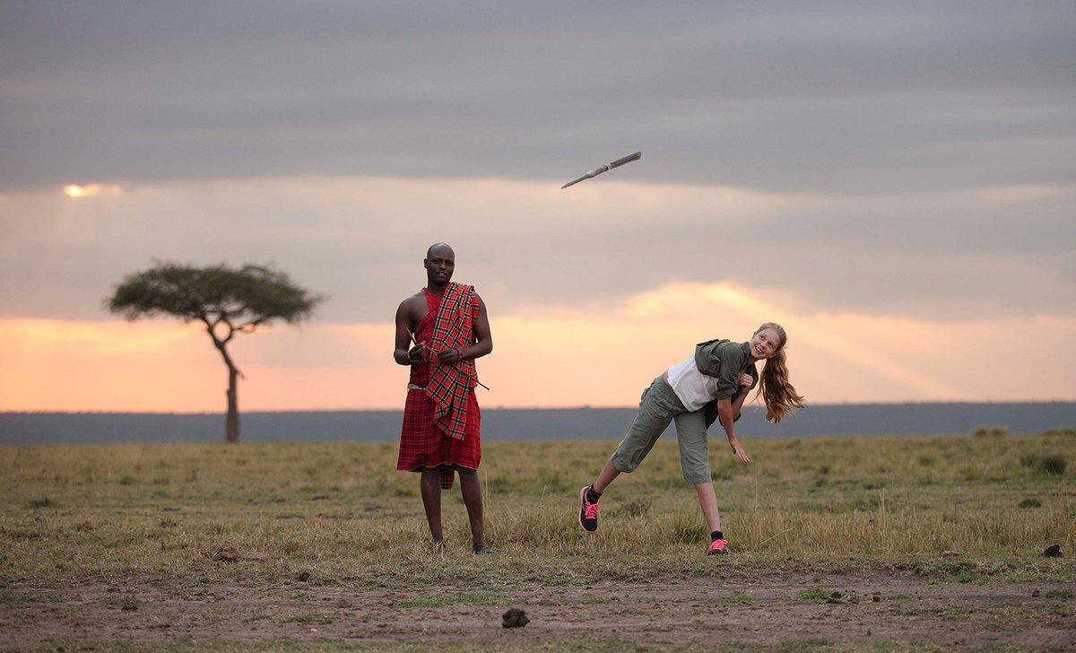 Girl throwing spear with maasai warrior on safari
