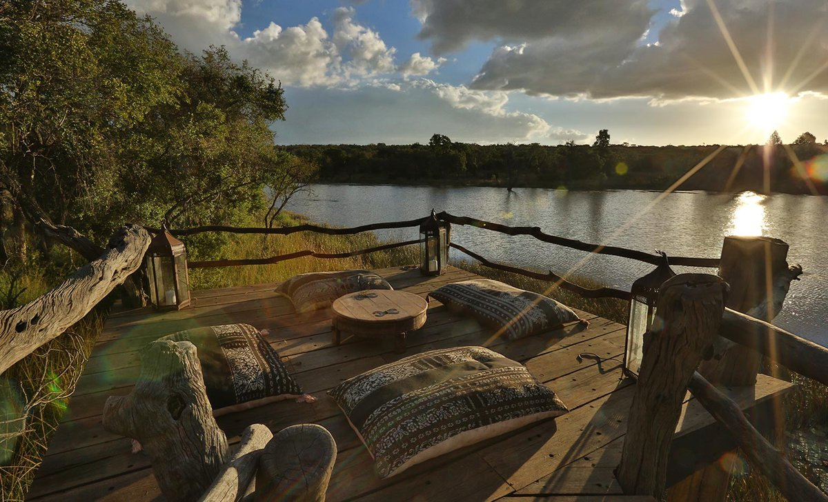 Leobo lodge raised platform viewing deck over lake at sunset