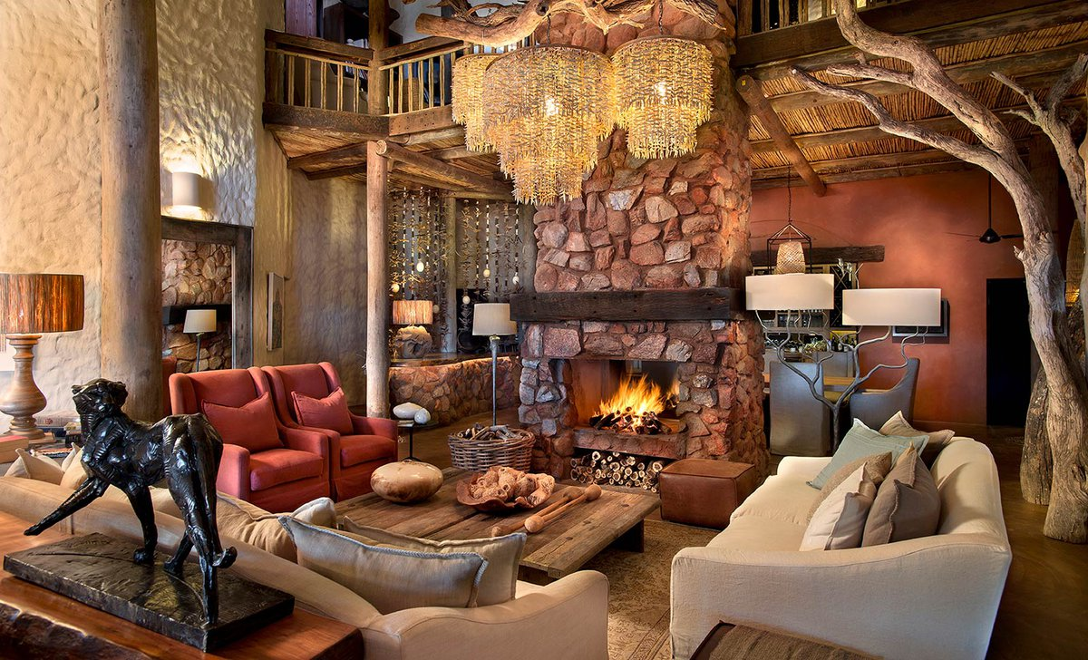 Luxurious lounge with large stone fireplace in Tarkuni House