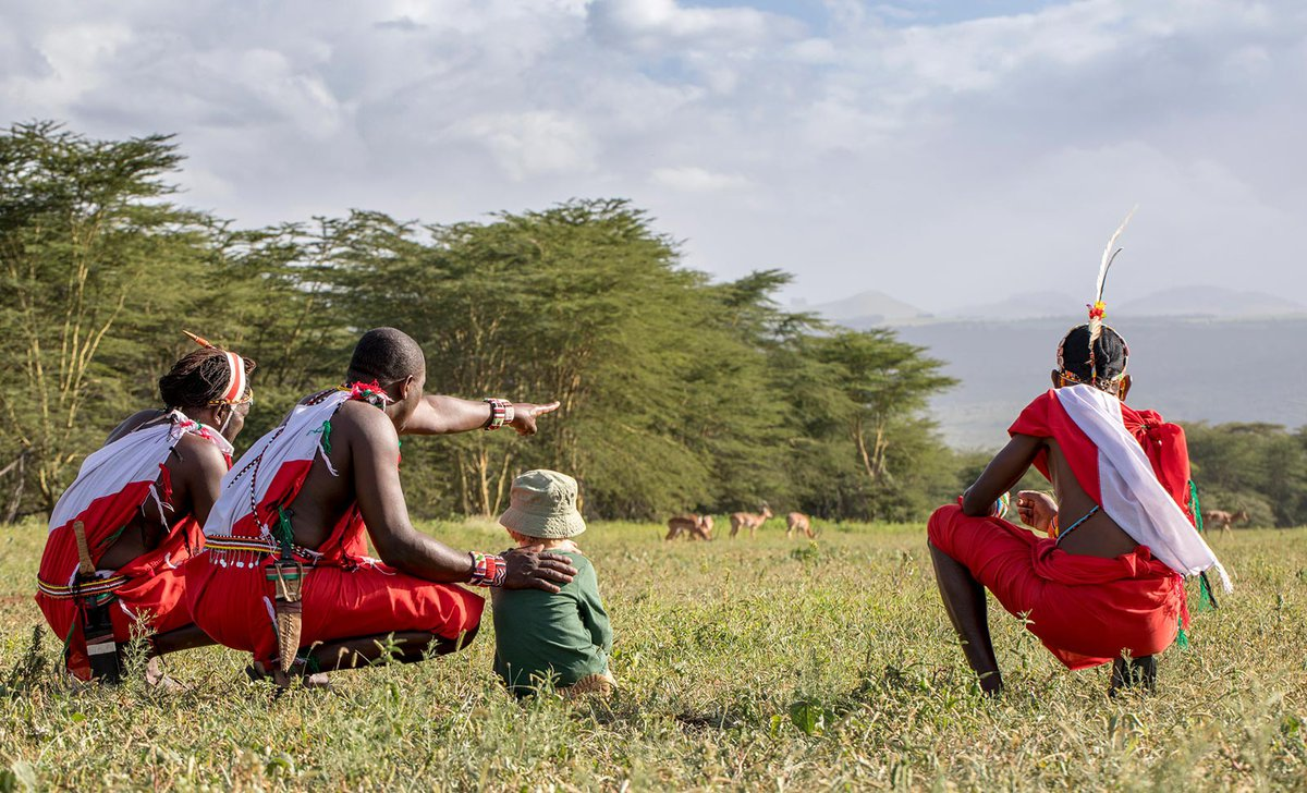 Boy with Maasai warriors watching antelope