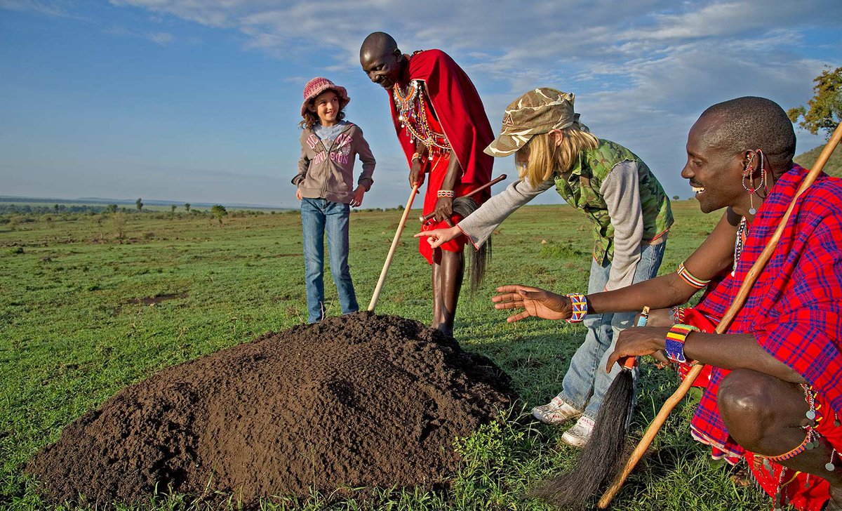Maasai guides teaching children about termite mound