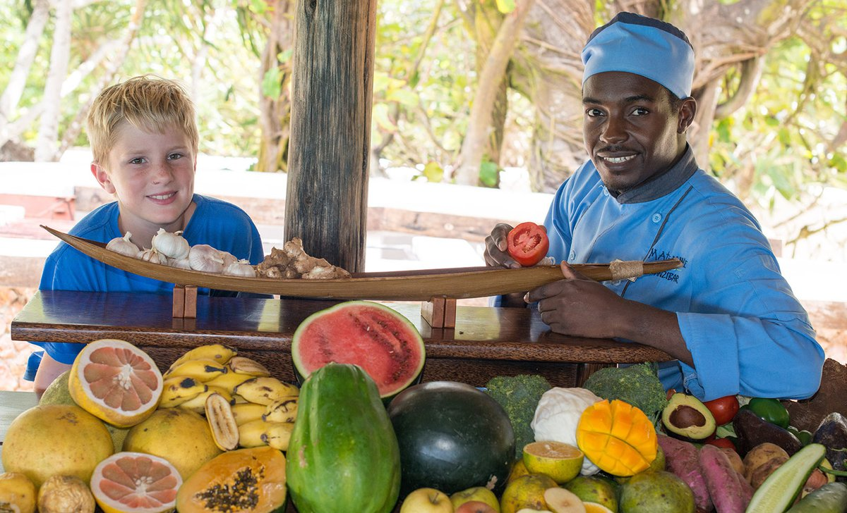 Boy and chef with fresh fruits