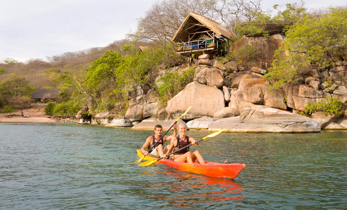 Kayaking at Mumbo Island in front of cliffside villas