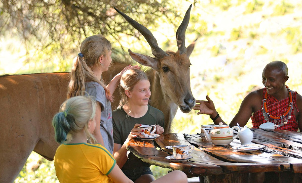 Family eating lunch with Maasai man