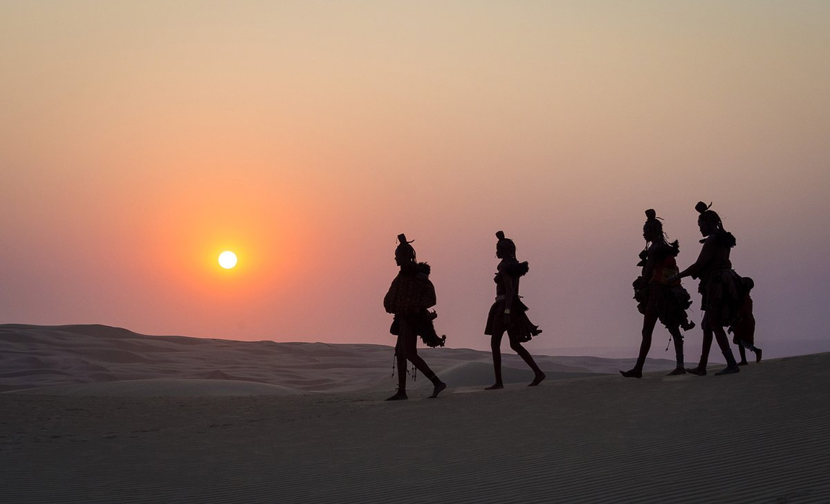 Himba people walking across dunes at sunset