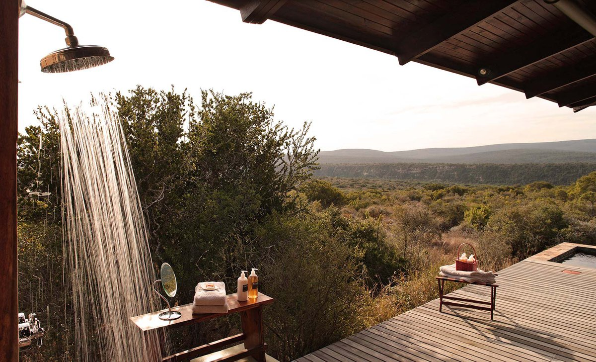 Outdoor shower with view at Kwandwe Ecca Lodge overlooking bushveld landscape