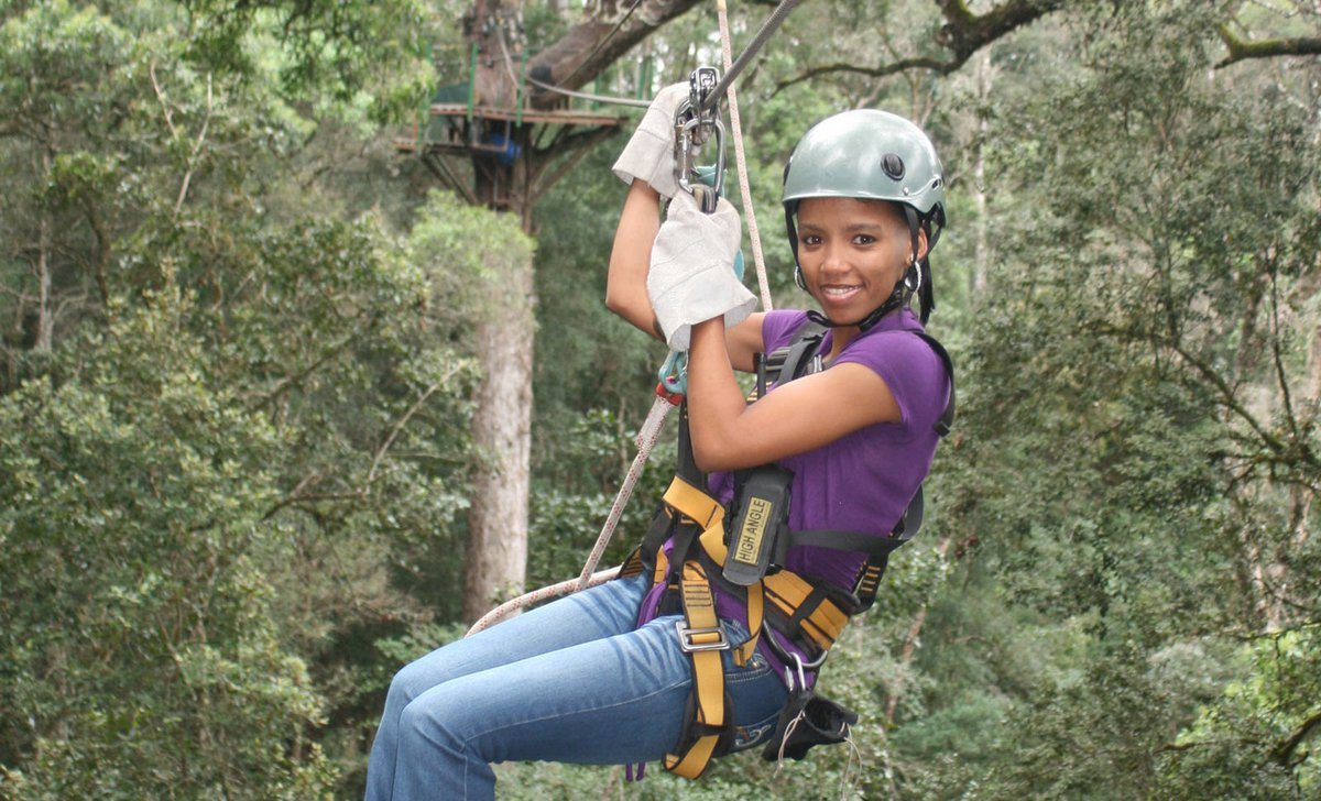 Teenage girl ziplining through nature reserve forest