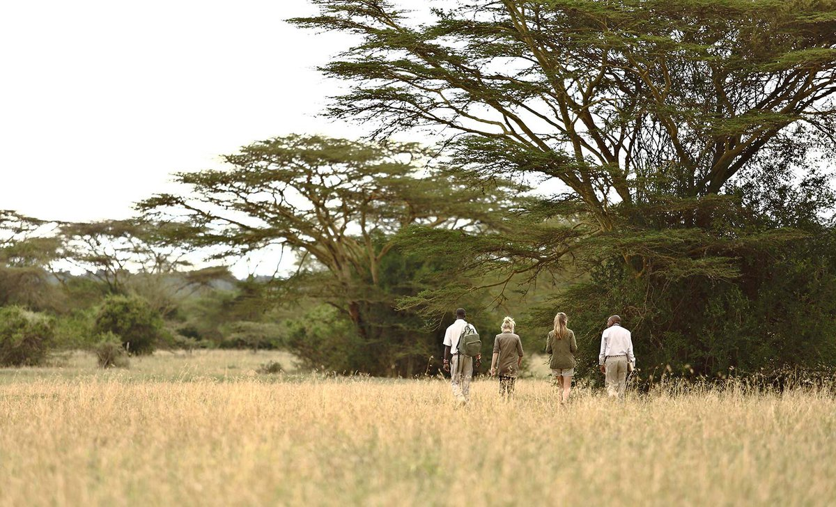 Teenage girls on walking safari with guides at Solio Lodge in Kenya