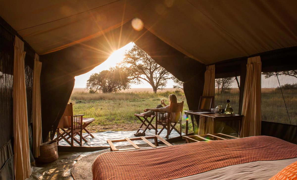 woman-relaxing-tent-view-serengeti-safari-camp-tanzania