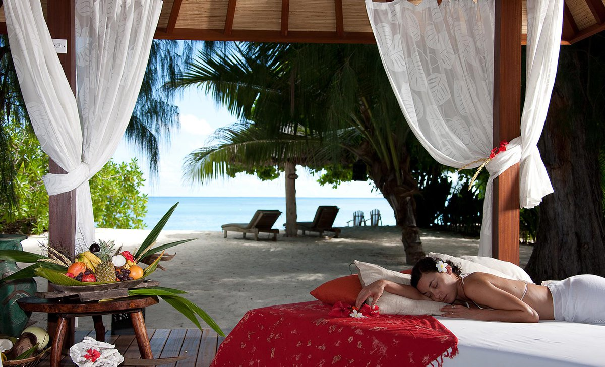 Woman relaxing in front of beach view, Denis Island, Seychelles.