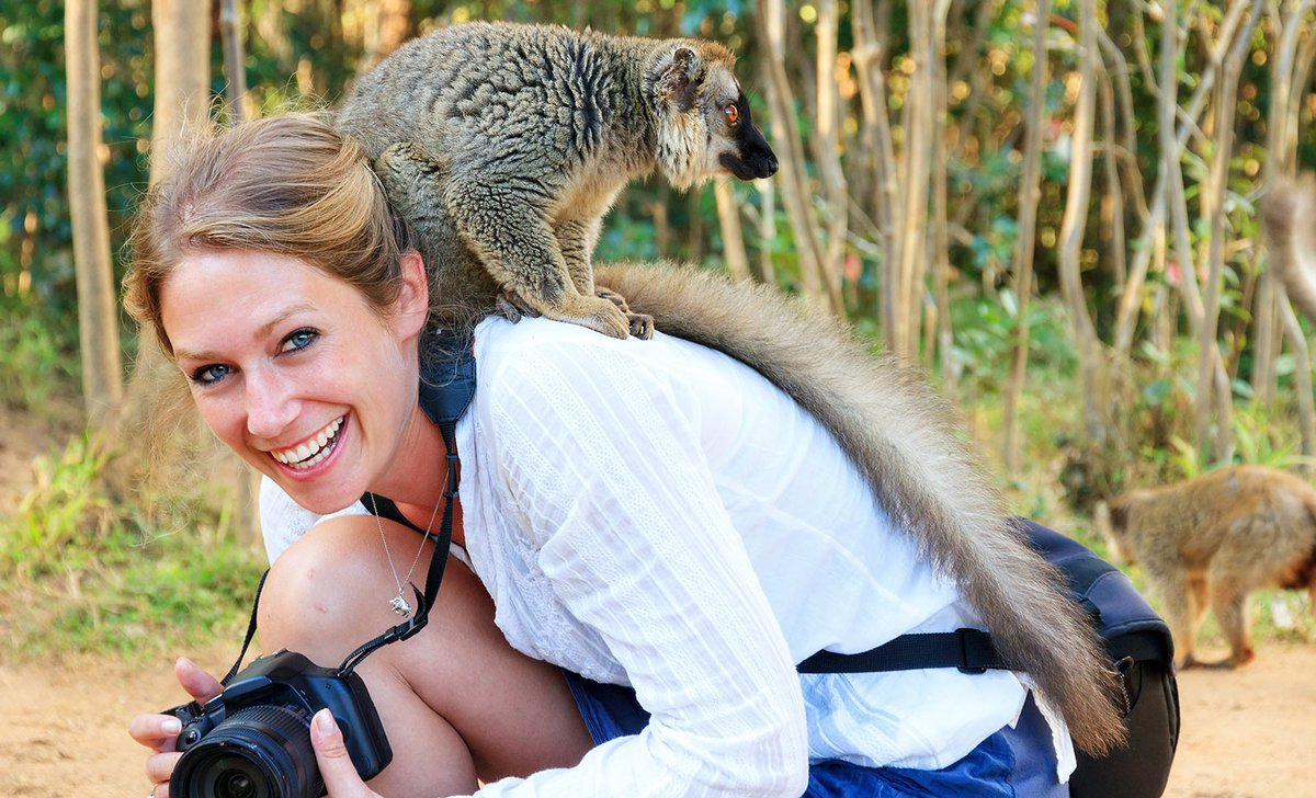 Woman with red fronted brown lemur on her back