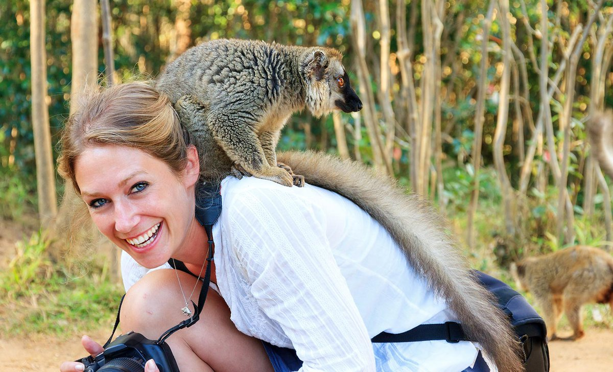 Woman with a lemur on her back in Madagascar.
